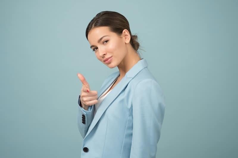 woman wearing blue office wear pointing onto the camera while standing in the blue wall