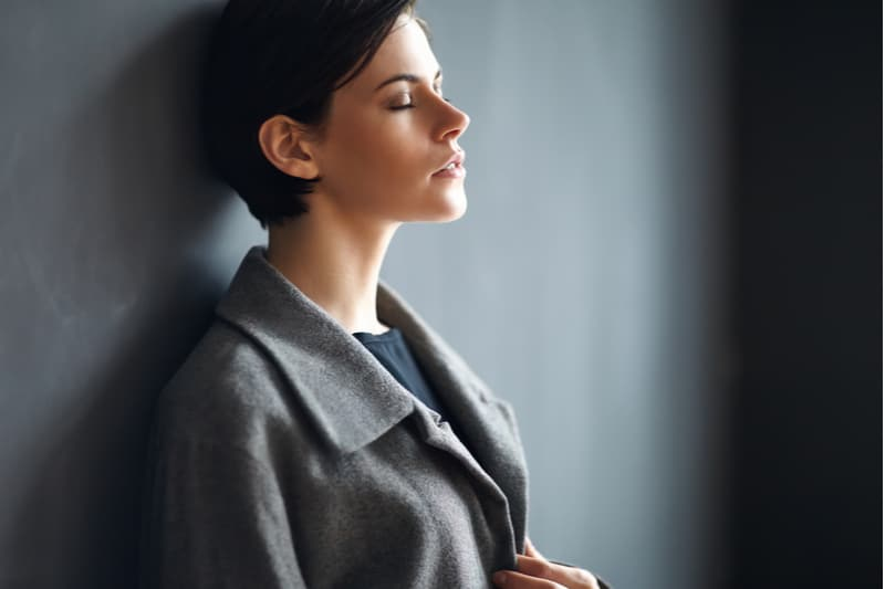 woman wearing gray business wear leaning on the gray wall closing her eyes