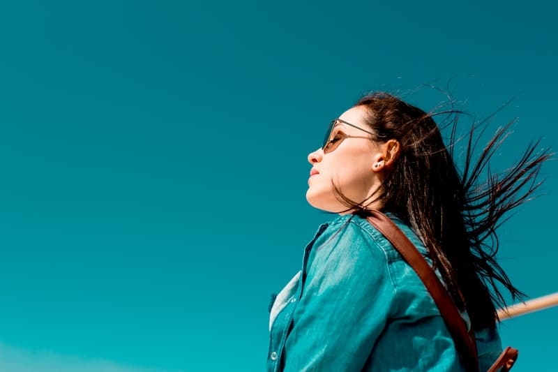 woman wearing shades closing her eyes wearing aquamarine blue top with sky of the same hue