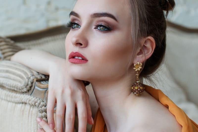 woman wears make up and big earrings dressed elegantly