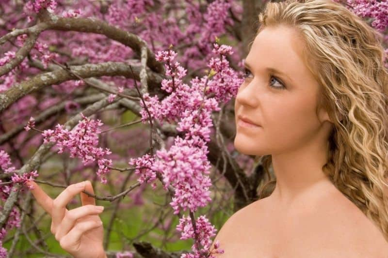 woman with innocent face standing against a tree with pink flowers