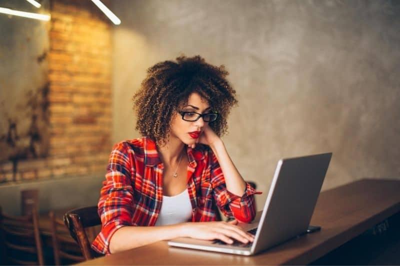 woman working at laptop indoors wearing eyeglasses