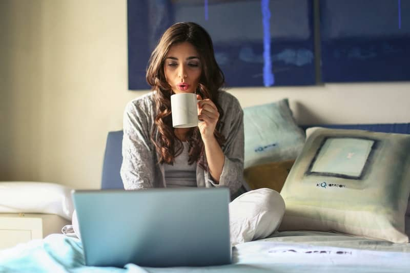 woman working in bed with her laptop while drinking hot beverage