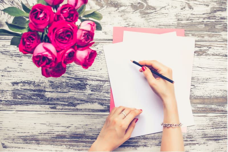 woman's hand writing a letter on the table with vase of red roses