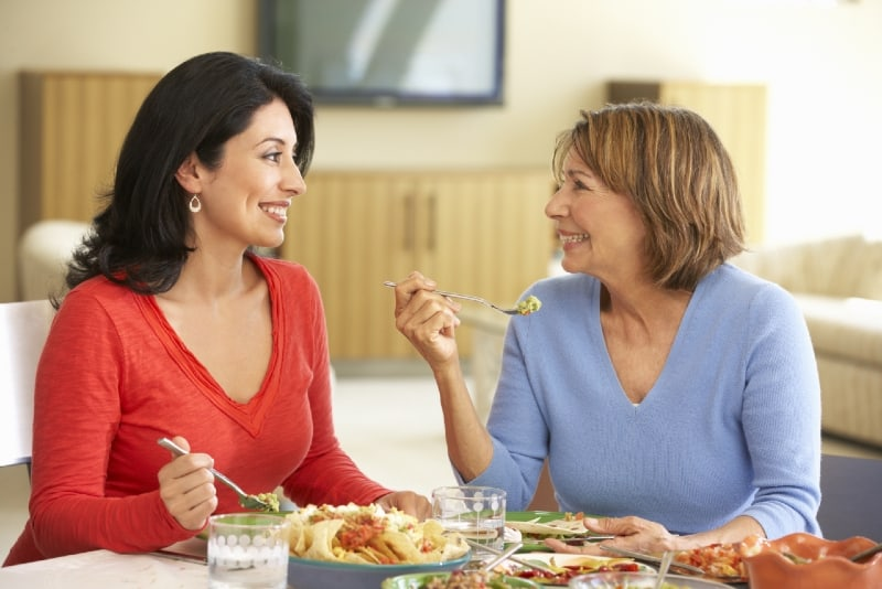 two smiling women having lunch while sitting at table