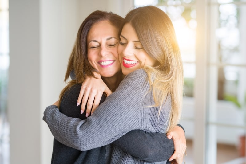 two smiling women hugging while standing indoor