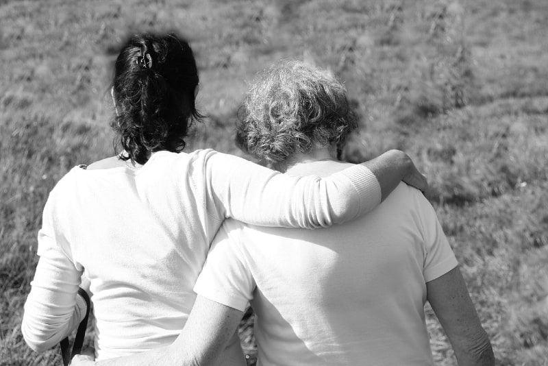 two women in white tops hugging outdoor