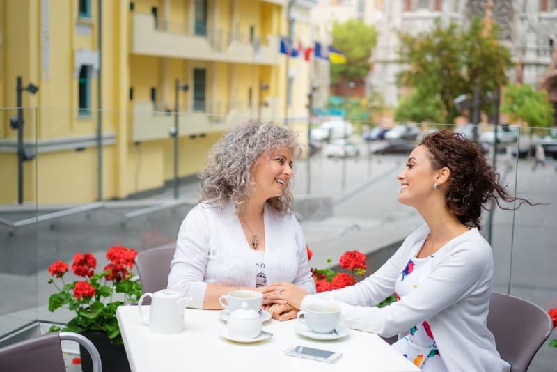 two smiling women holding hands while sitting at table outdoor