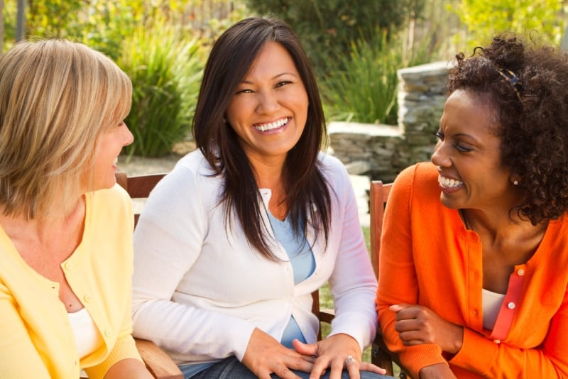 three women sitting on chairs and talking outdoor