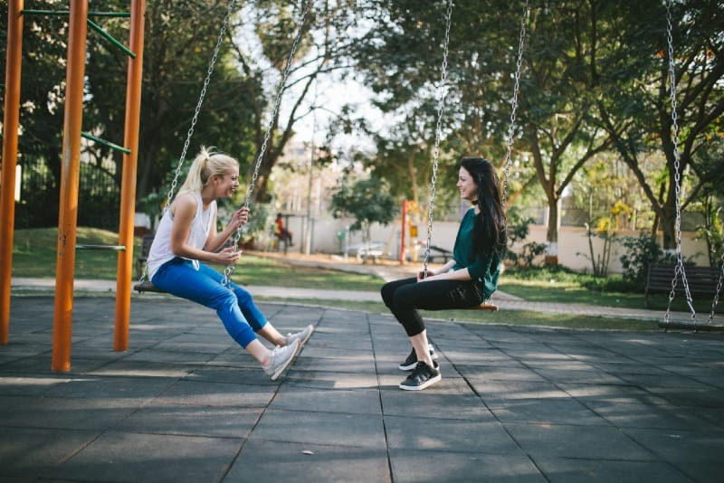 two smiling women sitting on swing in park