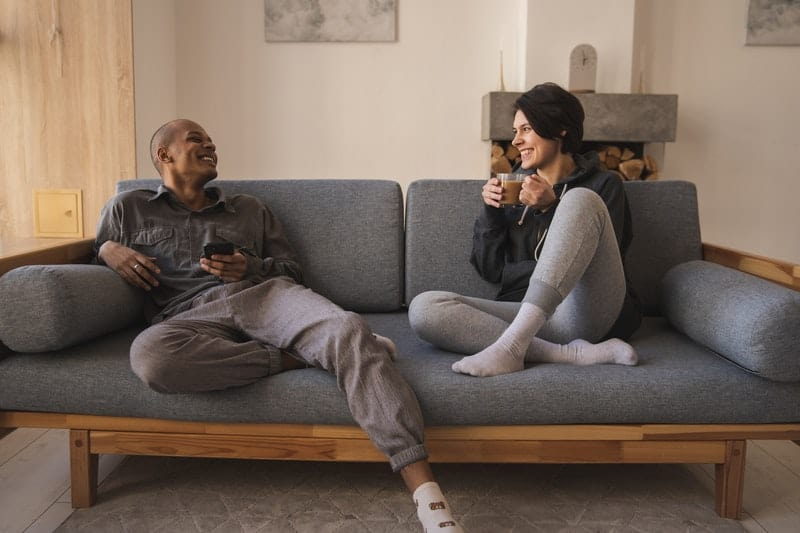 young cheerful diverse couple relaxing and talking in a gray couch