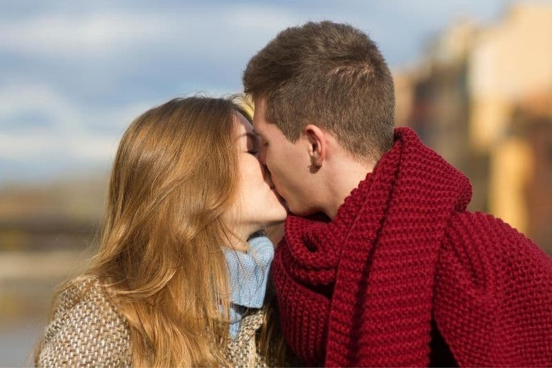 young couple kissing on cold days outdoors