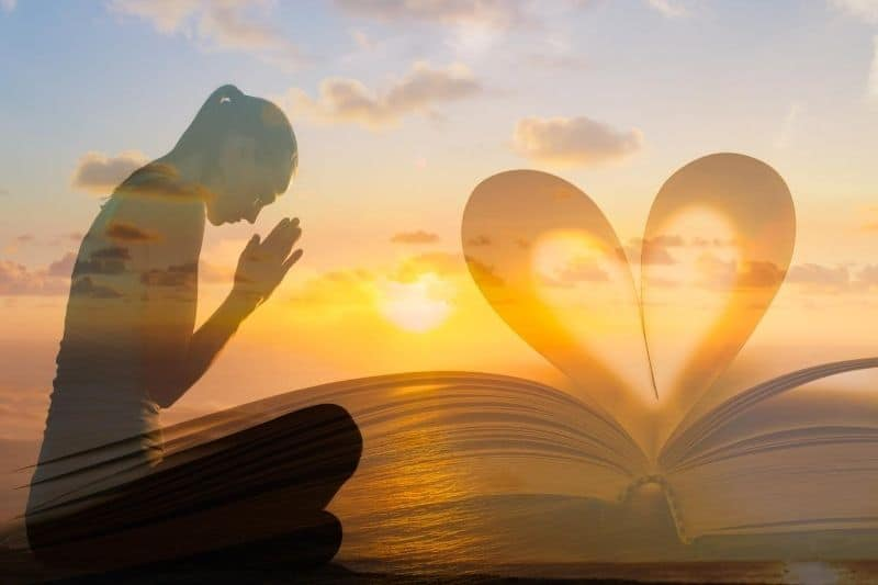 young female praying beside a bible in heart shaped against sunset