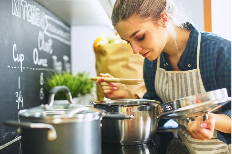 young woman cooking in the kitchen smelling the food from the caserole