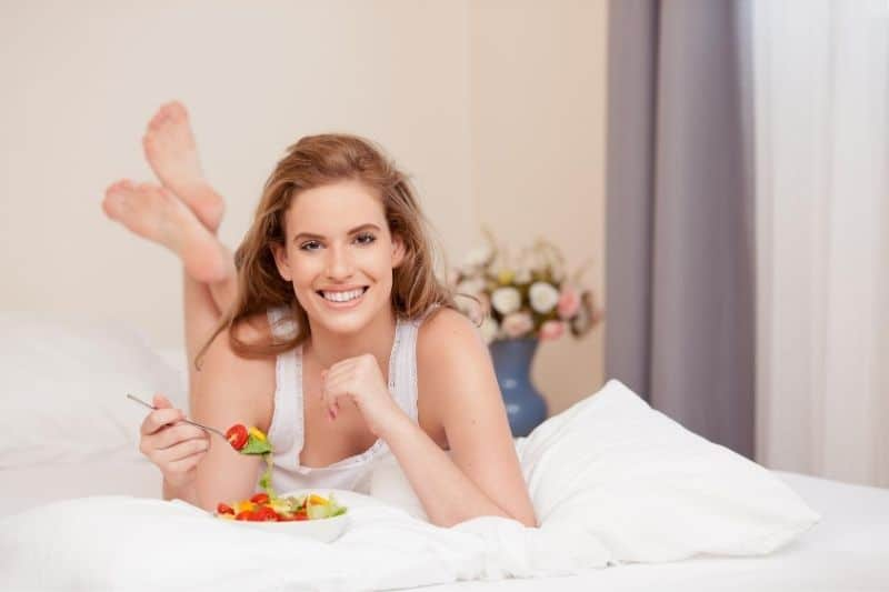 young woman eating healthy foods on bed in the hotel