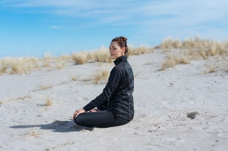 young woman meditating sitting in the sandy dune