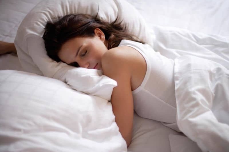 young woman sleeping soundly in white linen bed