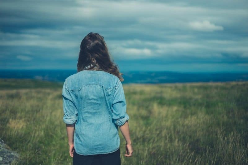 young woman standing in the middle of the field during windy day