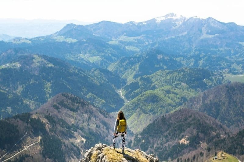 young woman stands in the mountain bringing a backpack