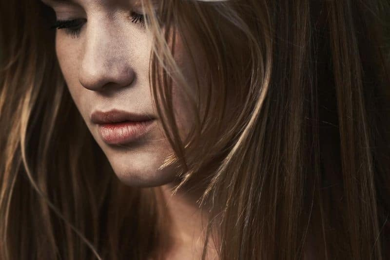 young woman's face in focus with hair partly cover her face