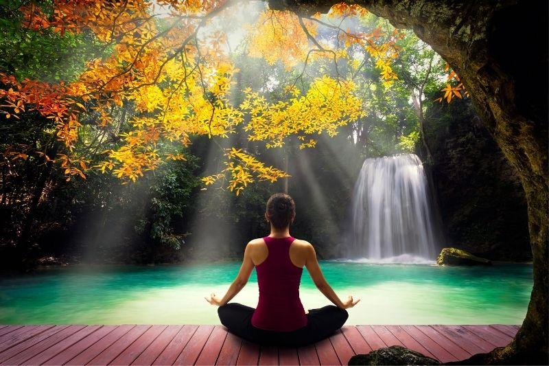 young woman posing yoga near a beautiful nature and waterfalls