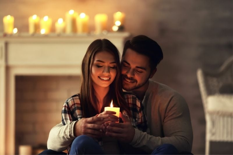 happy young couple burning candle at home