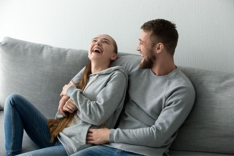 couple laughing hard inside the living room with gray sweater in a gray couch
