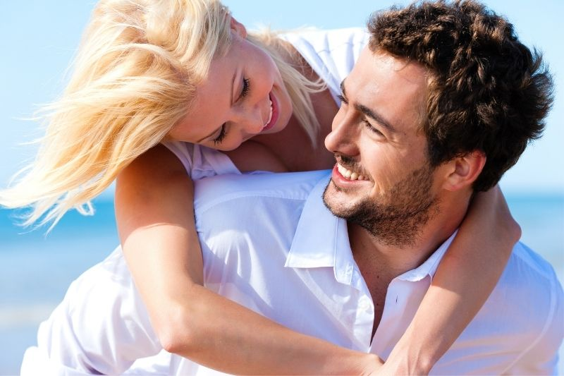 caucasian lovers having a piggyback and enjoying under the sun in the beach