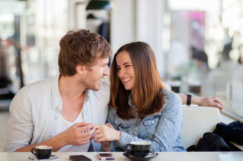 cheerful couple talking inside a cafe with their coffee