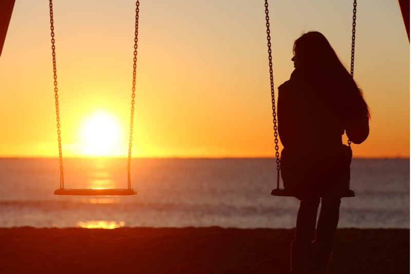 silhouette of a woman sitting on a swing alone looking at an empty swing beside her against the sunrise near the beach