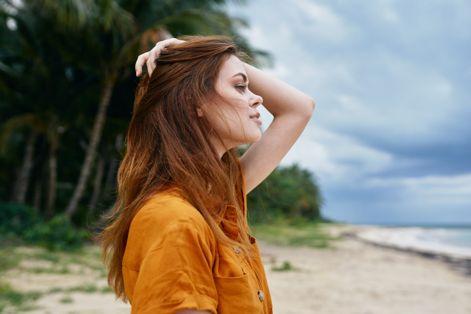 a beautiful red-haired girl in a yellow T-shirt stands on the beach