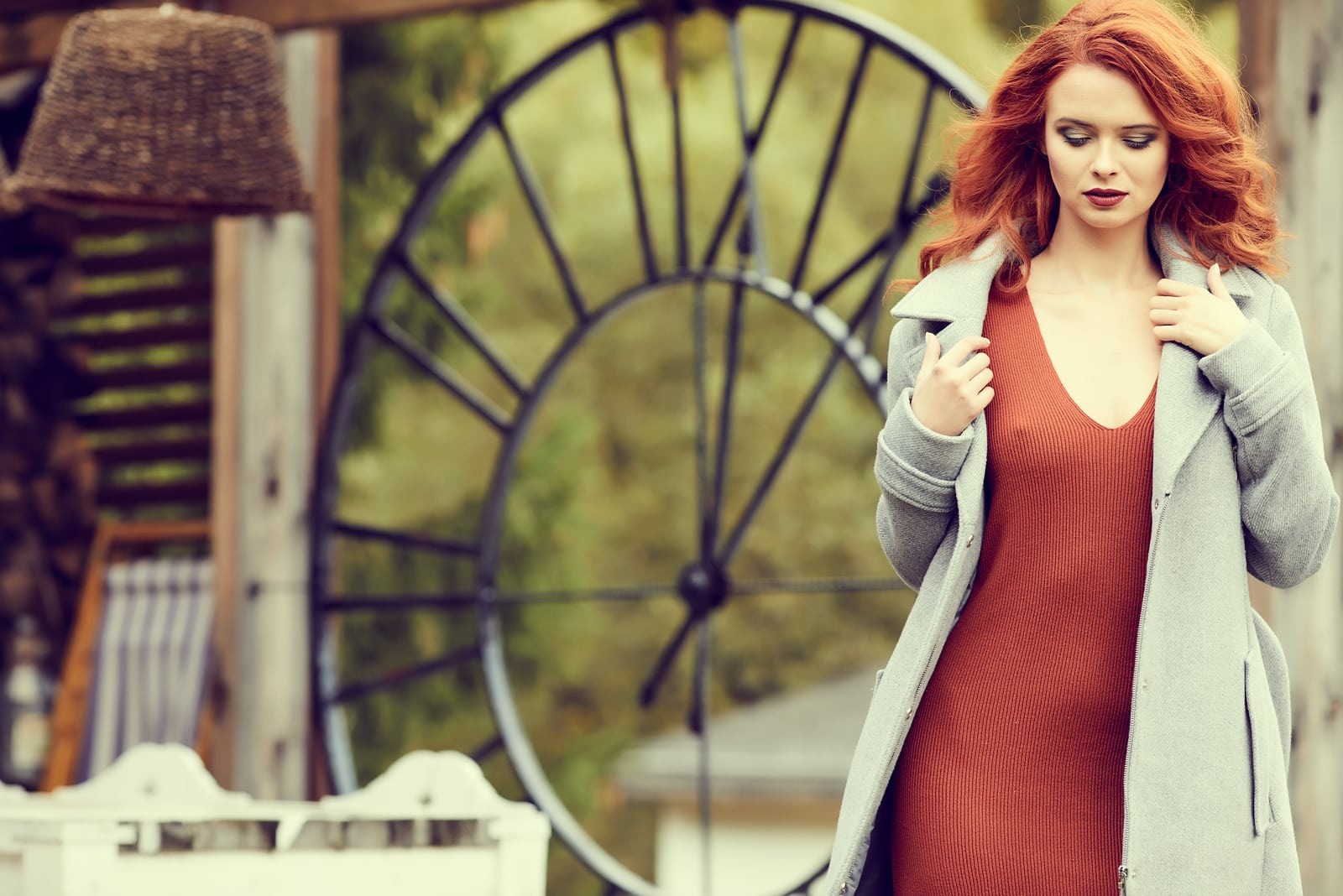 a beautiful red-haired woman in a burgundy dress and gray coat walks