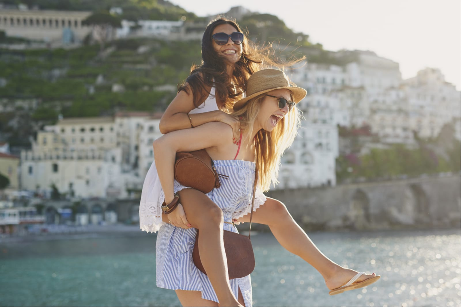 a smiling woman carries another woman on her back and having fun on the beach