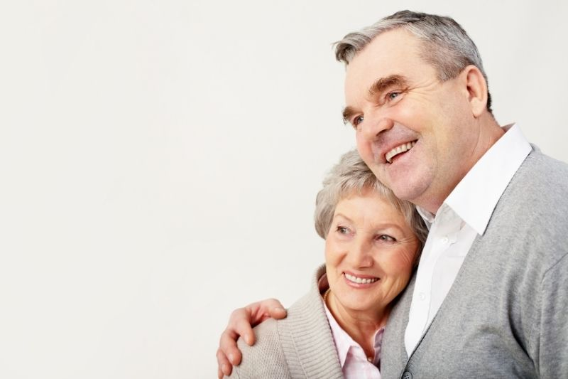 adult couple hugging wearing same shade of gray top standing against white background