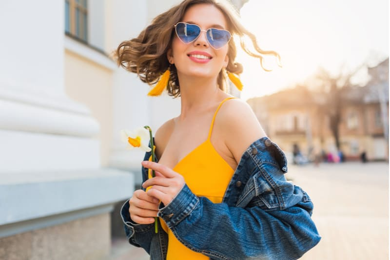 beautiful and fun loving woman with short wavy hair wearing yellow top + blue denim jacket