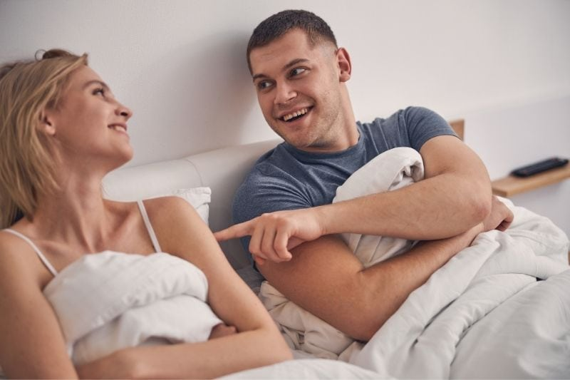 beautiful couple laughing while lying in bed