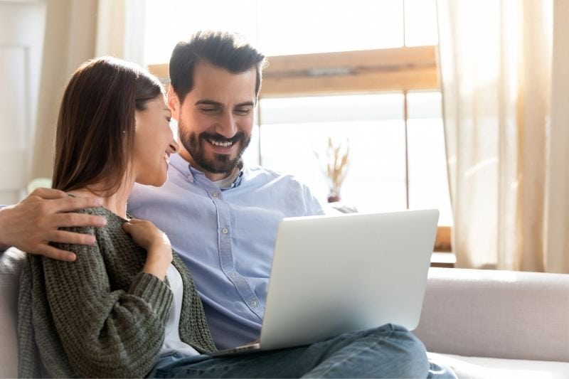 beautiful couple watching movie in a laptop inside the living room