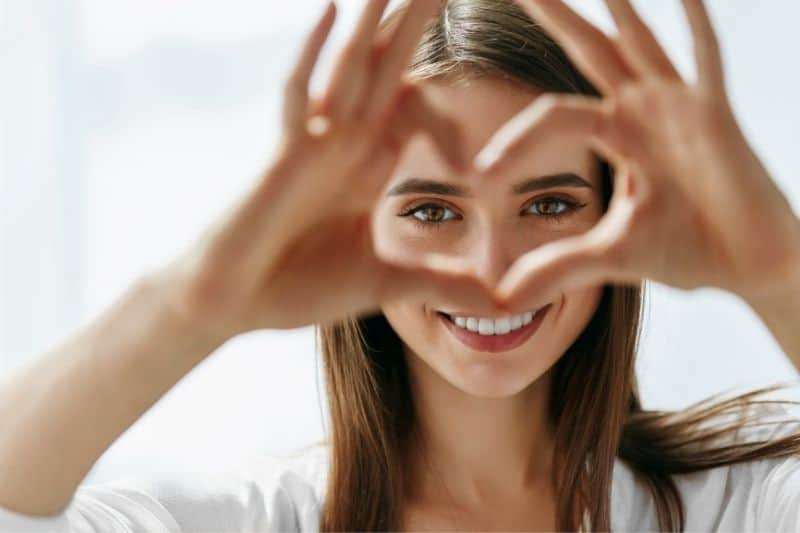 beautiful happy woman showing love signs near her eyes