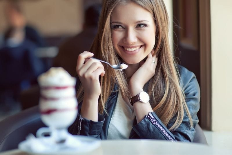 beautiful woman eating dessert smiling while looking and giggling