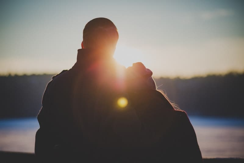 behind of two lovers facing the sunset/sunrise near a body of water
