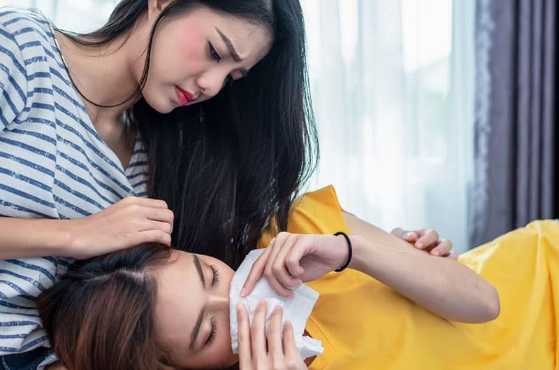 best friend comforting woman crying lying down on her lap
