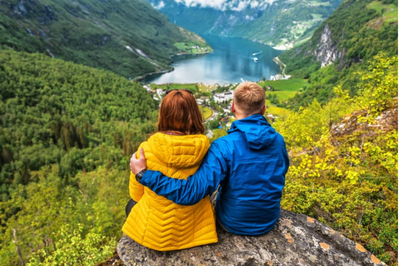 blue yellow couple sitting on a rock overlooking a body of water in the midst of the mountains