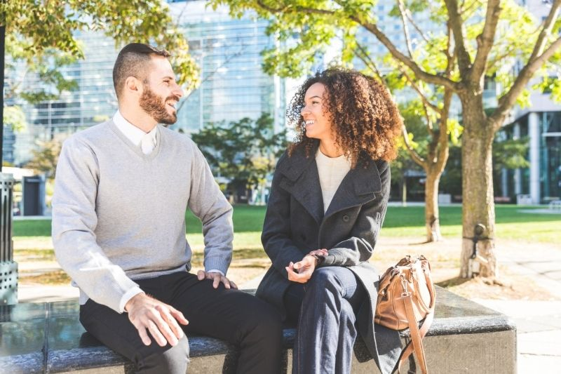 business woman and man talking and sitting in the bench outdoors
