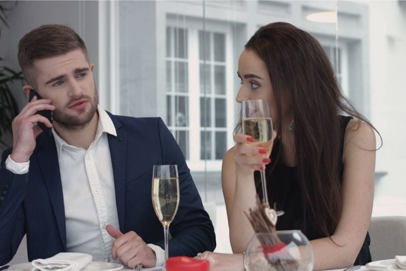 busy man on the phone while dating and a bored woman looking at the man and holding glass with wine