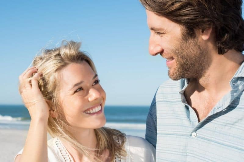 cheerful man looking at a woman smiling near the body of water