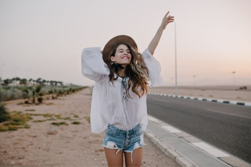 cheerful young woman raising her hand and holding hat standing beside the highway