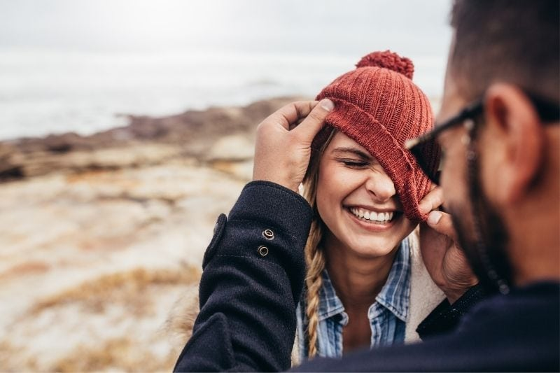 close photo of a couple laughing putting the bonnet on the woman incorrectly outdoors