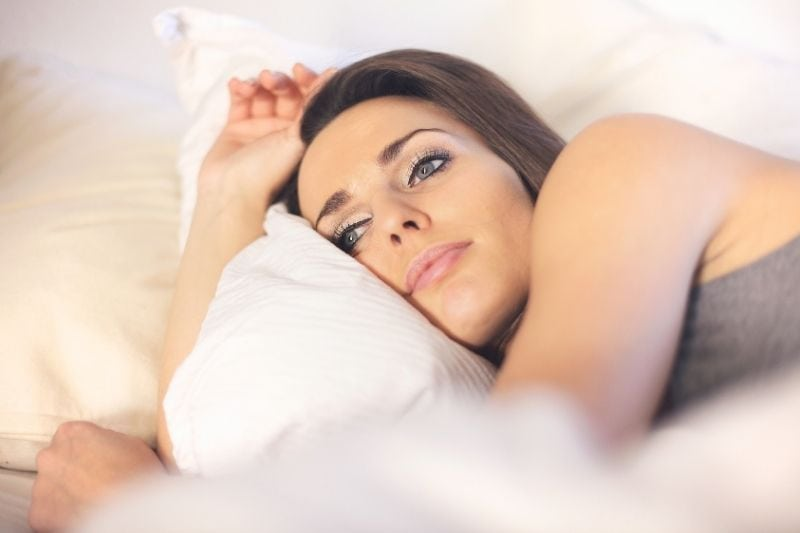 close up image of a pensive woman lying on bed