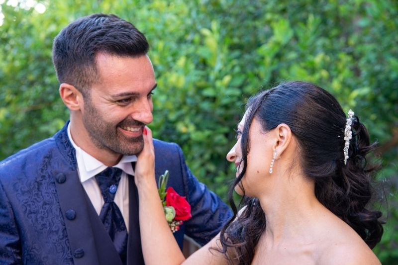 close up photo of couple laughing wearing formal wear outdoors