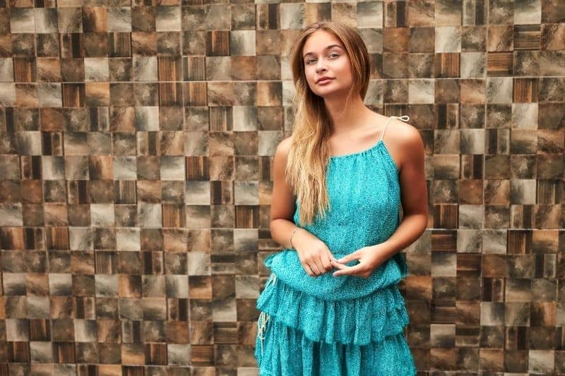 confident woman in blue green dress standing against a knitted wall